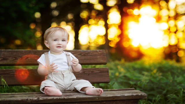 Baby Boy sitting on a Bench in beautiful Light